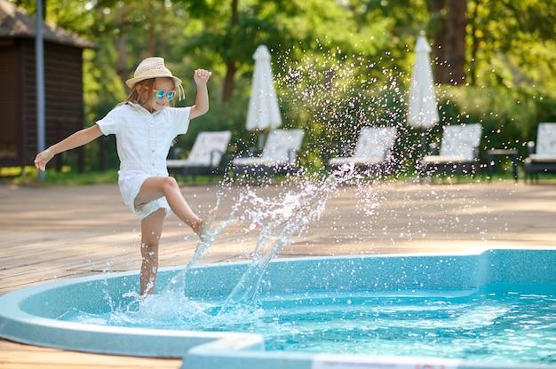 Милая блондинка маленькая девочка возле бассейна