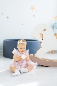 분홍색 드레스를 입은 귀여운 파란 눈의 한 살짜리 아기가 작은 흰색 공을 손에 들고 어린이 방 바닥에 앉아 있습니다