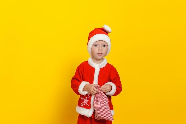 산타클로스 옷을 입은 귀여운 소년이 선물이 든 가방을 손에 들고 깜짝 놀라 카메라를 바라보고 있다