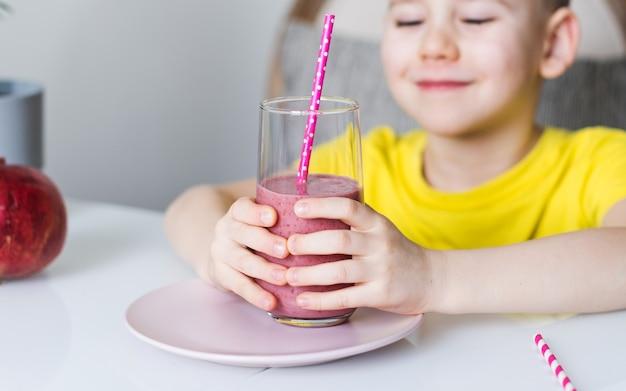 かわいい男の子が手にベリーのスムージーを持っています。健康食品の概念。スペースをコピーします。
