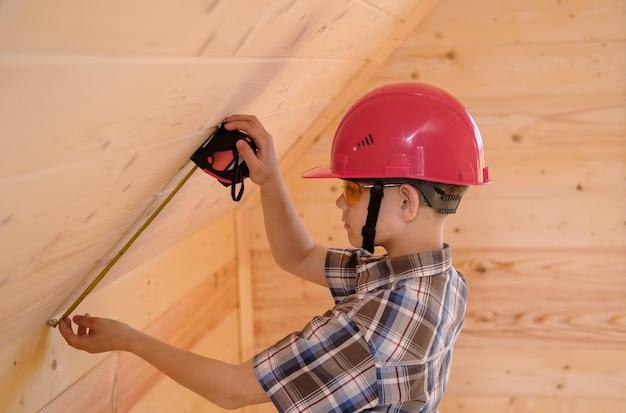 보호용 헬멧과 안경을 쓴 귀여운 소년이 건설 테이프 측정 값으로 새 목조 주택의 벽을 측정합니다. 목조 주택 건설 및 장식