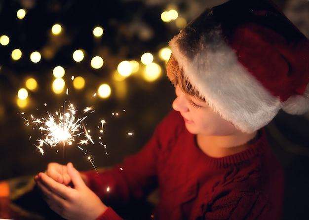 Милый мальчик в шапке санта-клауса держит горящие бенгальские огни на фоне желтых огней и хвойного дерева.