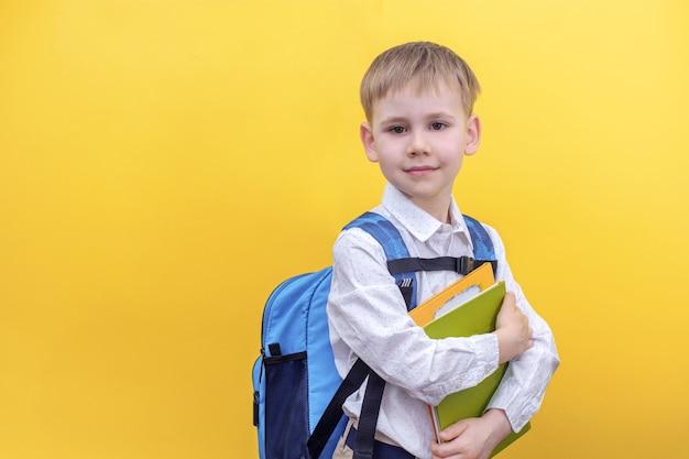 Милый мальчик в рубашке с рюкзаком на спине держит учебники на желтом