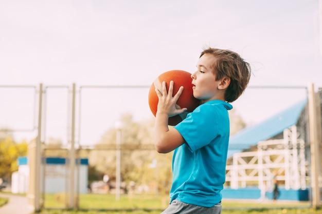 スポーツユニフォームを着たかわいい男の子がバスケットボールを手に持って投げる準備をしている、スポーツ