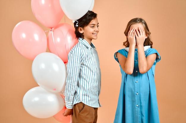 스트라이프 셔츠에 귀여운 소년은 고립 된 파란 드레스에 곱슬 머리를 가진 귀여운 소녀에게 분홍색과 흰색 풍선을 제공합니다