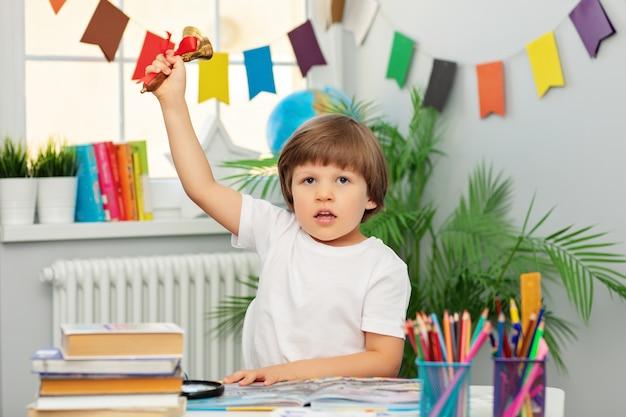 Милый мальчик в белой футболке сидит за школьной партой и звонит в колокольчик с красной лентой