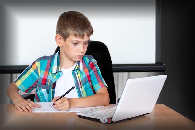 Милый мальчик сидит за столом, смотрит в ноутбук, пишет домашнее задание или готовится к экзамену. концепция снова в школу. копировать пространство