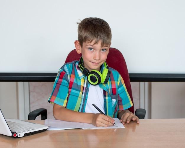 Милый мальчик сидит за столом, смотрит в ноутбук, пишет домашнее задание.