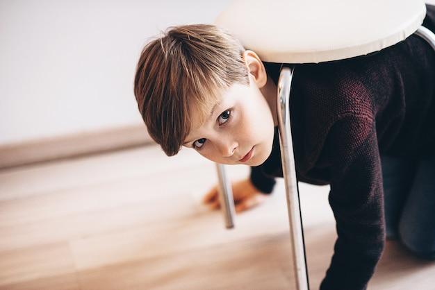 귀여운 소년 아이가 거북이 소프트 포커스인 척 등을 대고 바닥에서 놀고 있다