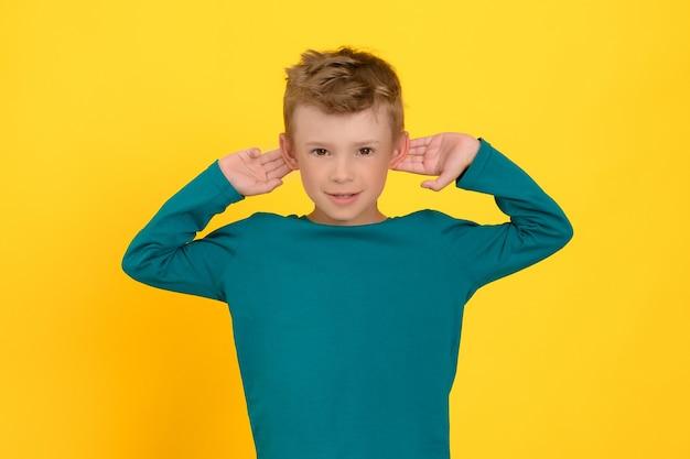 귀여운 소년은 기분이 좋아져서 더 나은 미소를 들을 수 있기를 바라며 손으로 귀를 찔러본다