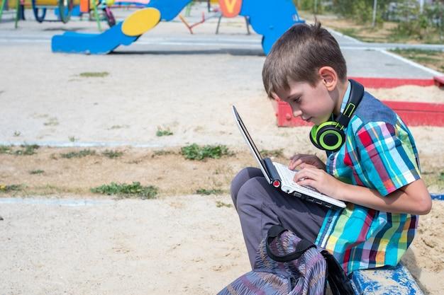Симпатичный мальчик-школьник в повседневной одежде занимается за ноутбуком на детской площадке, рядом лежит школьный портфель.