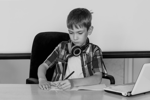 Симпатичный мальчик сидит за столом, смотрит в ноутбук, левой рукой пишет домашнее задание. концепция снова в школу. концепция исследования левой руки. копирование пространства, черно-белое