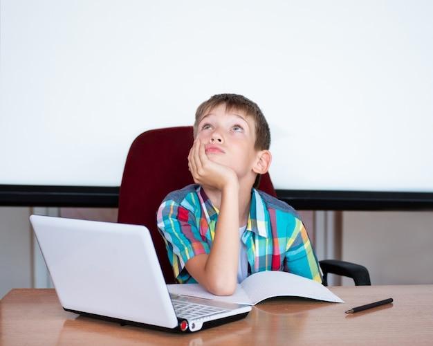 귀여운 소년이 탁자에 앉아 올려다보며 숙제를 기억합니다. 그 소년은 숙제를 배우지 않았습니다. 개념 학교, 가정 교육, 원격 교육 돌아가기. 복사 공간
