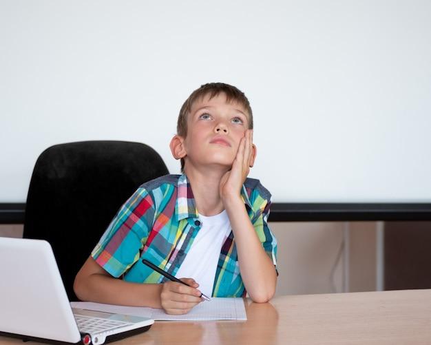 Симпатичный мальчик сидит за столом, смотрит вверх, вспоминает домашнее задание. мальчик не выучил домашнее задание. концепция снова в школу, домашнее образование, дистанционное образование. копировать пространство