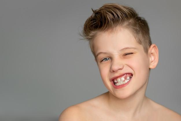 귀여운 소년이 한쪽 눈을 윙크하고 웃으며 들쭉날쭉 한 이빨을 보여줍니다.