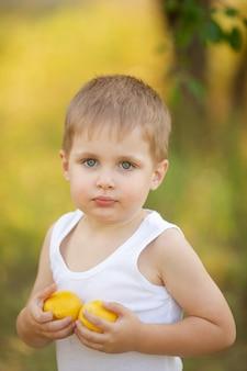木の下の庭で夏のレモンと白いtシャツのブロンドの髪のかわいい男の子