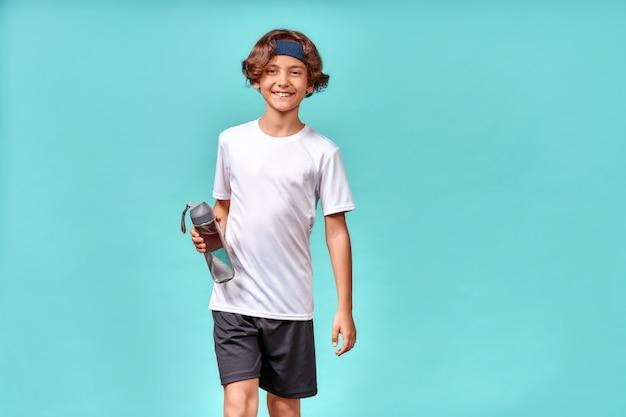 물 한 병을 들고 카메라를 보고 훈련이나 운동 후에 웃고 있는 귀여운 소년