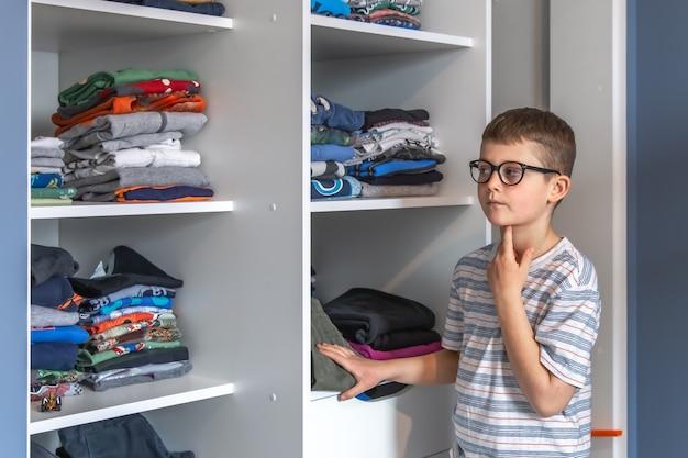 안경을 쓴 귀여운 소년이 옷장 근처에 서서 무엇을 입을 지 생각합니다.