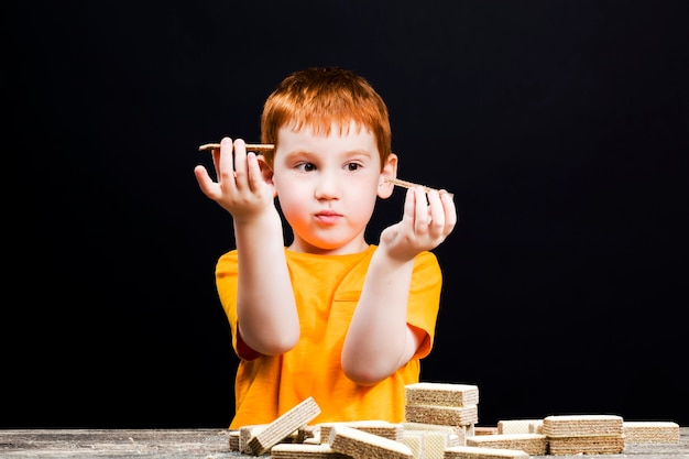 빨간 머리를 가진 귀여운 소년이 초콜릿 와플을 먹고 있고, 와플을 가진 소년이 디저트 중에 놀고, 소년은 과자에 만족합니다 프리미엄 사진