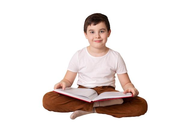 大きな開いた本を持っているかわいいブルネットの少年
