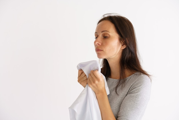 밝은 벽에 깨끗한 흰색 향기 셔츠를 들고 귀여운 백인 여자 의류에 대한 홈 케어의 개념
