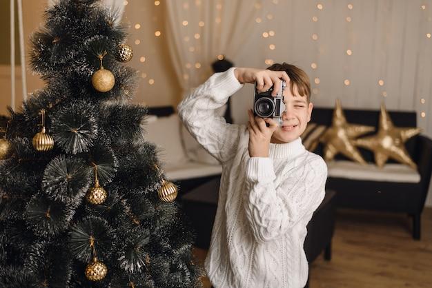 Милый ребенок фотографирует вас на ретро-фотоаппарат на фоне елки