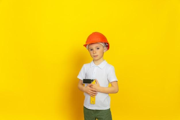 オレンジ色のヘルメットと白いtシャツを着た黄色い壁に真面目な表情のかわいい子供が立って、定規を手に測定器を持っています。職業の選択、エンジニア。