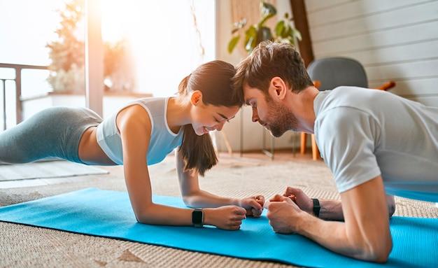 Милая парочка в спортивной одежде выполняет упражнения на ковриках в гостиной дома. здоровый образ жизни, спорт, йога, фитнес.