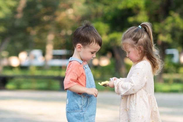 かわいい巻き毛の女の子は、キャンディーを開梱するのに役立ち、木の真ん中に立っている男の子を扱います