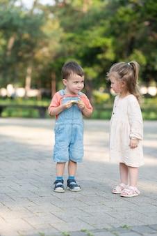 かわいい巻き毛の女の子がキャンディーの包装を解くのを手伝って、公園の中央で前に立っている男の子を扱います