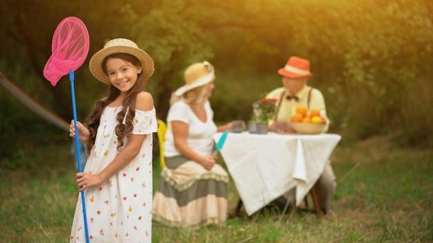 핑크 나비 그물과 sundress에서 귀여운 검은 머리 소녀.