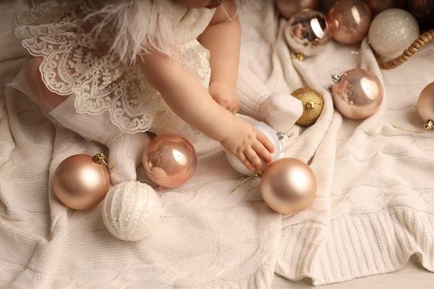 Симпатичная темнокожая девочка сидит на белом вязаном пледе и играет с елочными игрушками.
