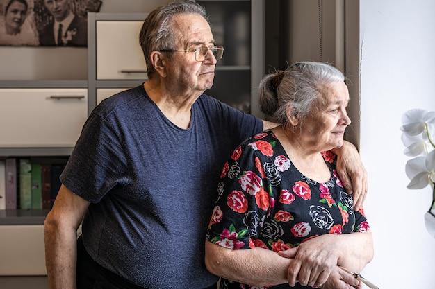 Милая пожилая пара стоит у окна и смотрит на кого-то в ожидании.