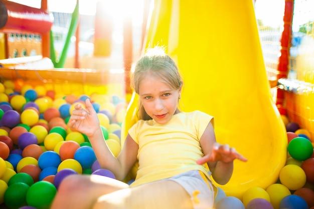 かわいいおかしい女の子は、柔らかくて明るい機器のある遊び場に座って、カメラに向かってカラフルなボールを投げます