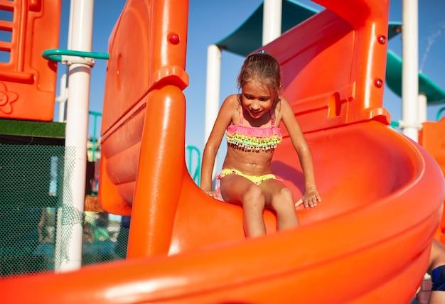 明るい水着を着たかわいい女の子がオレンジ色のスライドに座って、澄んだ水でプールに降りる準備をしています