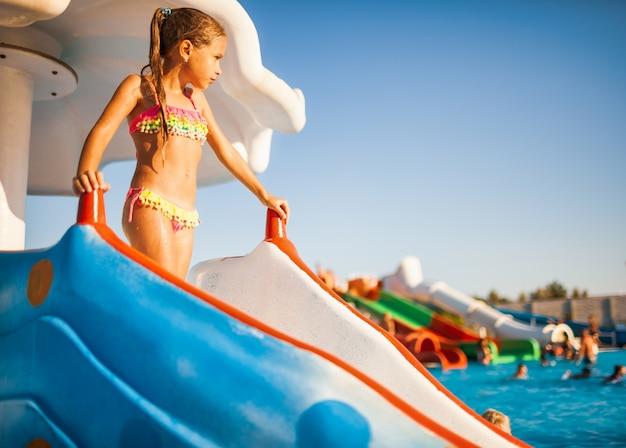 明るい水着姿のかわいい女の子がスライドの上に立って、そこから澄んだ透明な水があるプールに降りる準備をしています