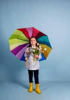 Милая девушка в плаще и резиновых сапогах держит букет тюльпанов и разноцветный зонтик на синем фоне с местом для текста
