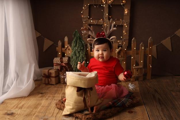 Милая девочка в красном новогоднем костюме достает елочные игрушки из мешка с подарками