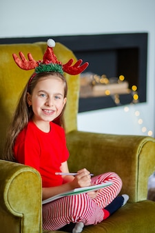 Милая девушка в шляпе санта пишет письмо к санте возле елки. счастливое детство, время для исполнения желаний.