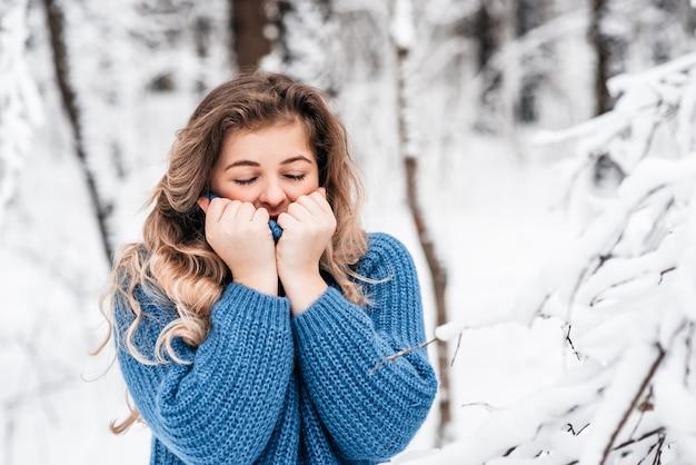冬の凍るような森や青いニットのセーターの公園でかわいい女の子。アクティブで楽しいライフスタイル