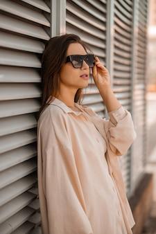 Милая девушка в бежевом и в солнцезащитных очках позирует