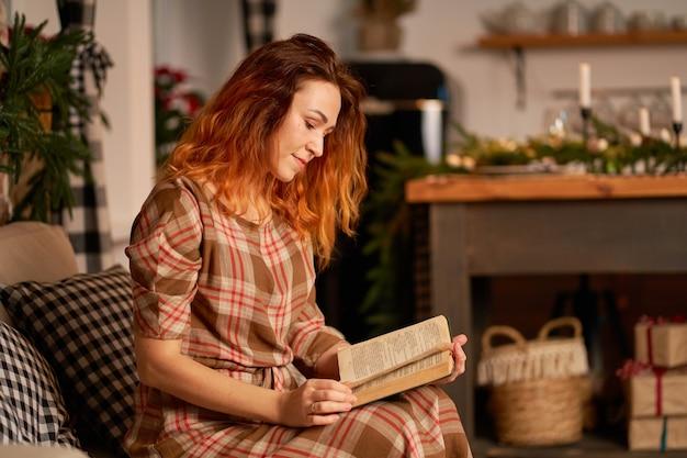 Милая девушка читает книгу в теплой и уютной атмосфере. концепция релаксации и уединения.