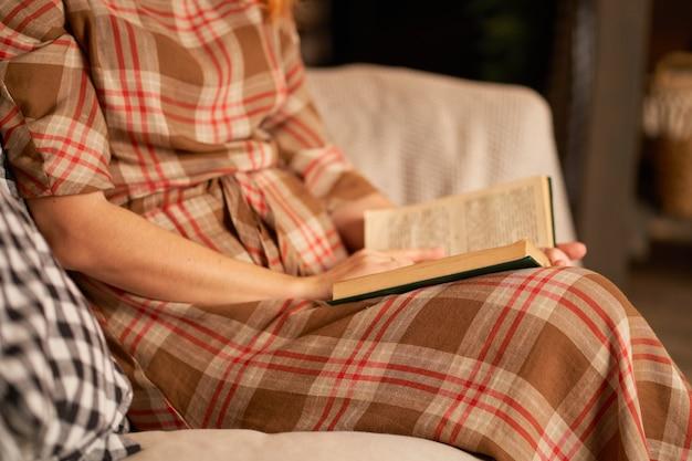 かわいい女の子が暖かく居心地の良い雰囲気の中で本を読んでいます。リラクゼーションとプライバシーの概念。