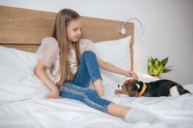Симпатичная девочка играет со своим щенком и смотрит, как ей нравится