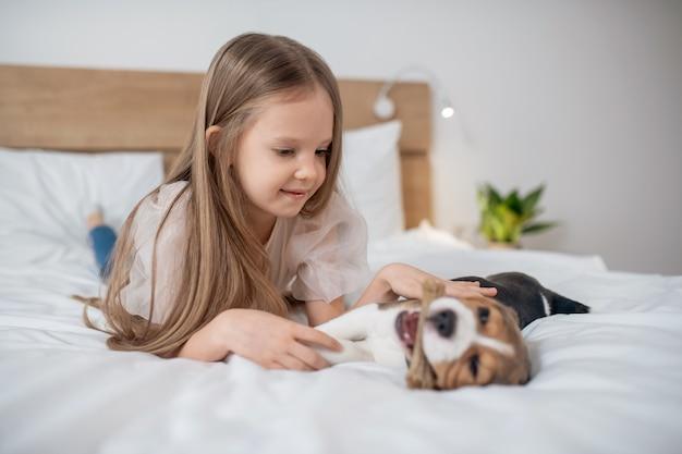 Милая девочка играет со своим щенком и выглядит счастливой