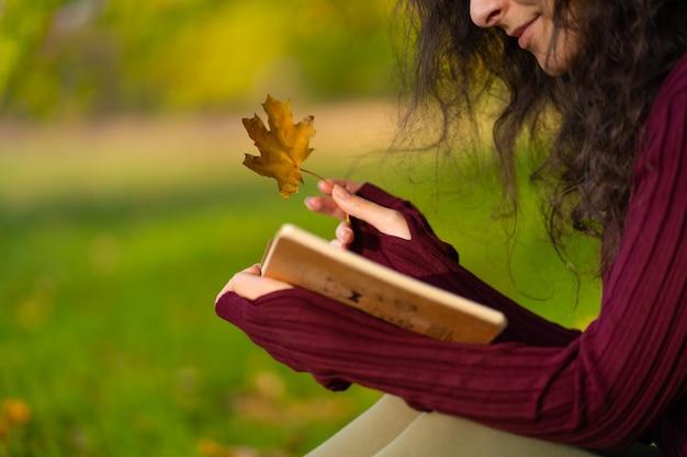 Милая девушка читает книгу и пьет кофе на зеленой лужайке в осеннем парке. осеннее настроение. уютное место, чтобы побыть наедине с собой.