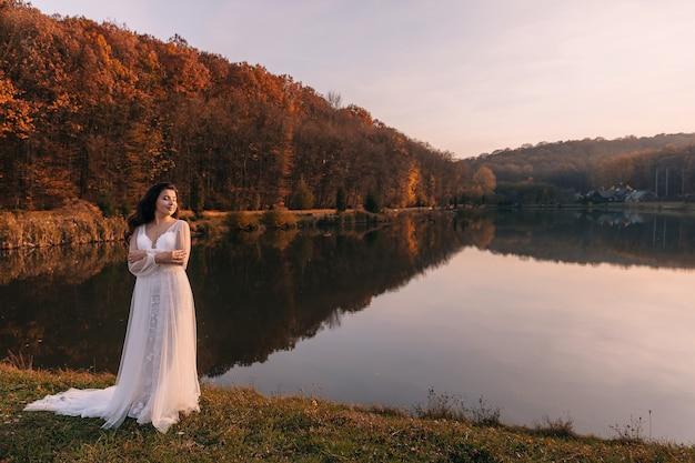 長い巻き毛のかわいい女の子が湖を背景に白いドレスを着て立っています