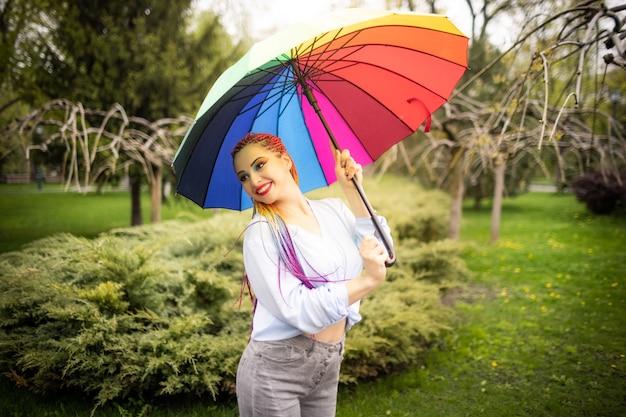 꽃이 만발한 봄 공원을 배경으로 무지개 우산을 들고 포즈를 취한 푸른 셔츠에 여러 가지 빛깔의 머리띠와 밝은 화장을 한 귀여운 소녀
