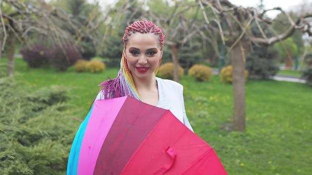 Милая девочка с разноцветными косами и ярким макияжем
