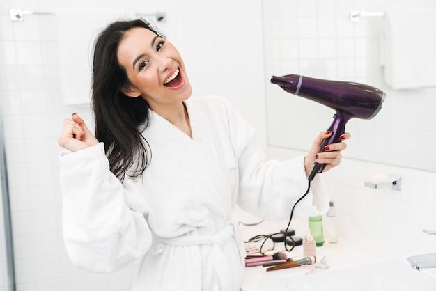 Милая счастливая смешная молодая женщина в помещении дома в ванной комнате сушит волосы с пением фена.